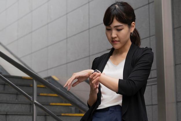 Вид спереди женщины, смотрящей на часы