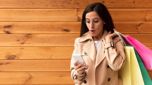 Вид спереди женщины, потрясенно смотрящей на свой телефон, держа сумки для покупок
