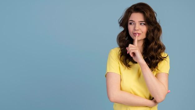 Вид спереди женщины, создающей шум тишины с указательным пальцем