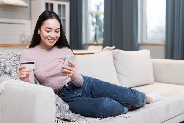 クレジットカードとスマートフォンを使用してオンラインで注文するソファの上の女性の正面図
