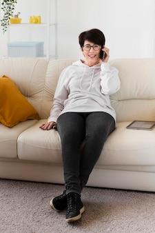 スマートフォンで話しているソファの上の女性の正面図
