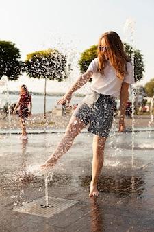 噴水で楽しんで屋外で女性の正面図