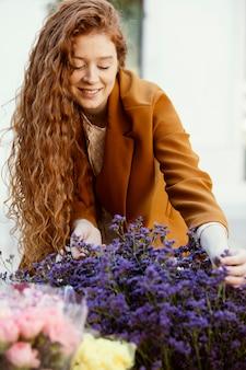 꽃의 부케와 함께 봄에 야외에서 여자의 전면보기