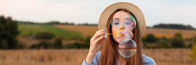 Вид спереди женщины на открытом воздухе, делая мыльные пузыри