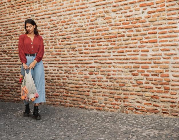 Вид спереди женщины на открытом воздухе с продуктовыми сумками и копией пространства