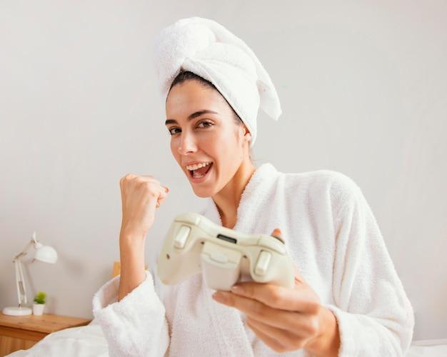 入浴後に自宅でビデオゲームをしている女性の正面図