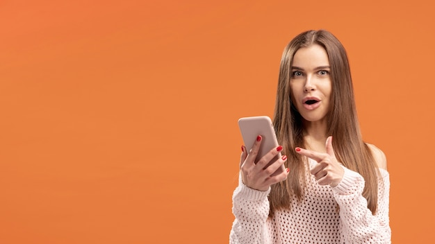 彼女が保持しているスマートフォンを指している女性の正面図