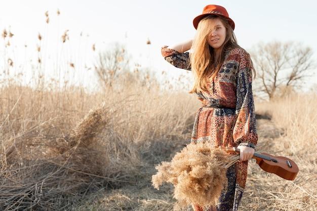 Вид спереди женщина позирует на природе с укулеле