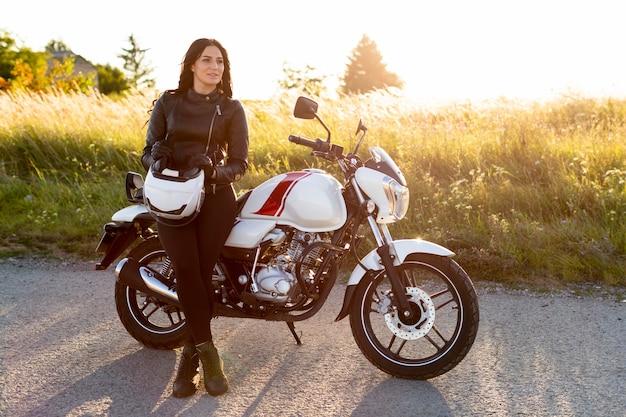 女性が彼女のバイクの横にポーズの正面図