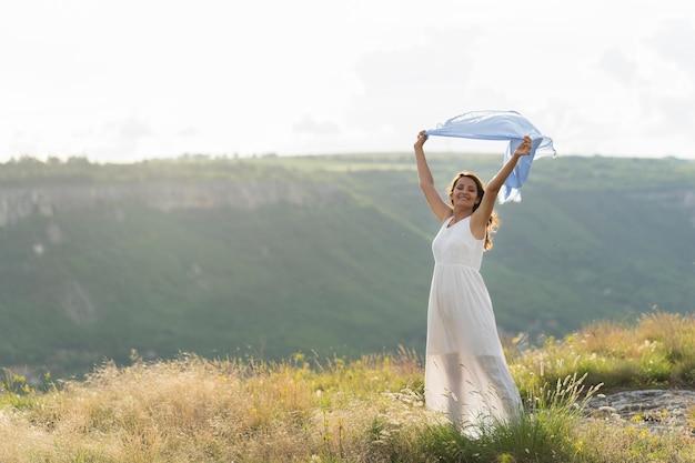 風の中でスカーフを屋外でポーズ女性の正面図