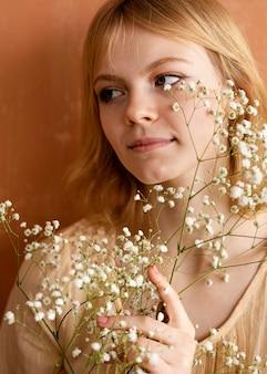 美しい花でポーズをとる女性の正面図