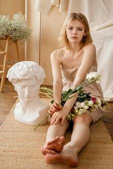 아름 다운 봄 꽃과 함께 포즈를 취하는 여자의 전면보기 프리미엄 사진