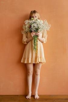 봄 꽃의 부케와 함께 포즈를 취하는 여자의 전면보기