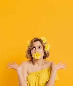 Вид спереди женщина позирует с цветком, прикрывая рот