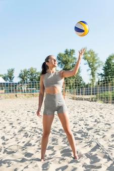 女性がビーチでバレーボールでポーズの正面図