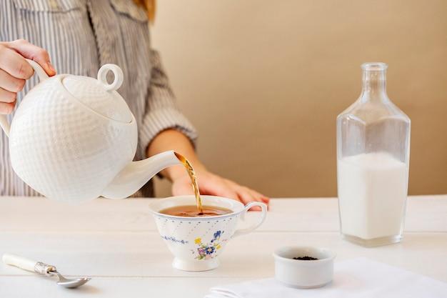Вид спереди женщины готовит чай с молоком