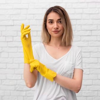 Вид спереди женщина готовится к уборке, надевая перчатки