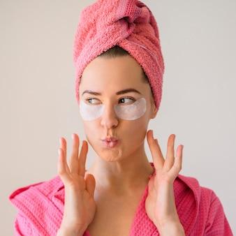 Вид спереди женщины поджимая губы при ношении глазных повязок