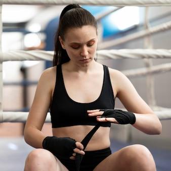 Вид спереди женщины надевают защитные перчатки рядом с кольцом