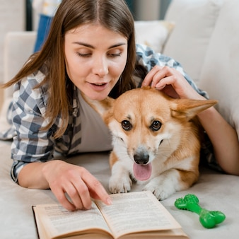 ソファの上の犬と一緒に本を読む女性の正面図