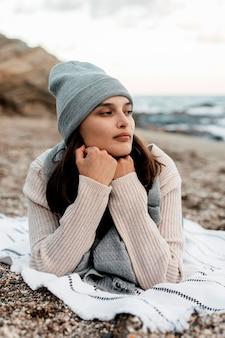 혼자 해변에서 휴식하는 여자의 전면보기