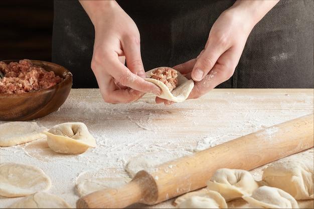 木製麺棒で肉団子を作る女性の手の正面図。