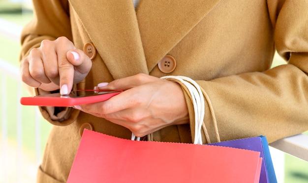 사이버 월요일에 스마트 폰으로 온라인 쇼핑하는 여자의 전면보기