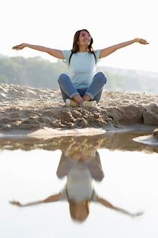 ビーチの砂の上に座っている女性の正面図
