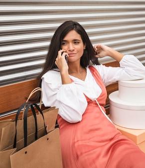 Вид спереди женщины, сидящей на скамейке с коробками