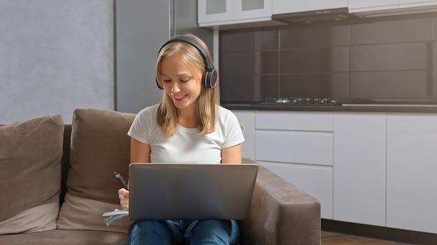 Вид спереди женщины, сидящей с ноутбуком и наушниками.