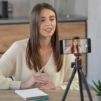 スマートフォンを使用してオンラインストリーミングする女性の正面図