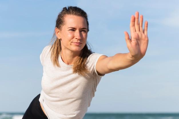 Вид спереди женщины, растягивающейся на пляже