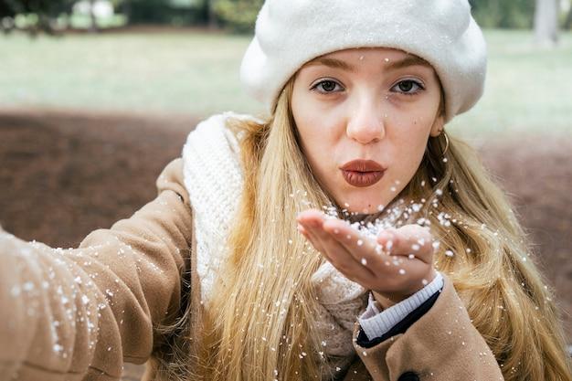 雪と冬の間に公園で自分撮りをしている女性の正面