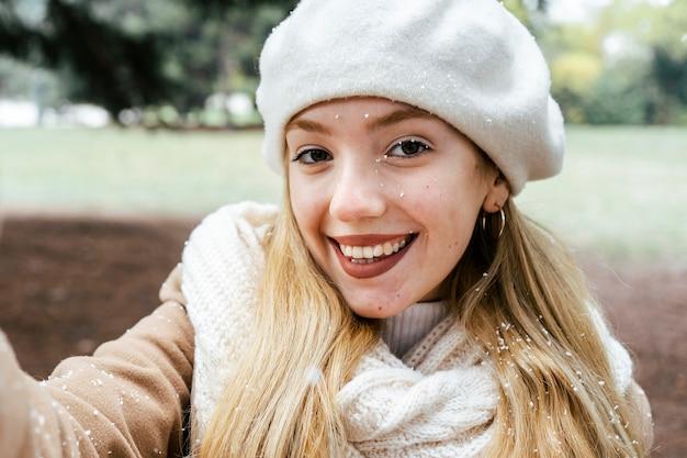 冬の間に公園で自分撮りをしている女性の正面図