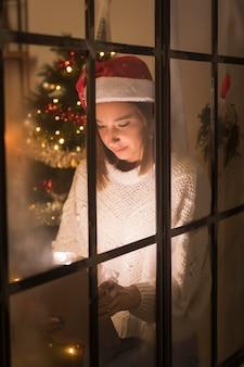 Вид спереди женщины через окно, глядя на планшет
