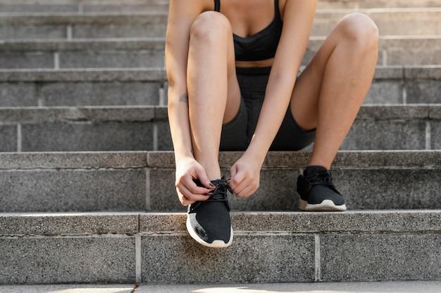 운동하기 전에 그녀의 구두 끈을 묶는 여자의 전면보기
