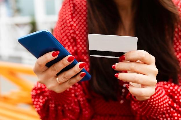 스마트 폰 및 신용 카드를 사용하여 온라인 쇼핑을하는 여성의 전면 모습 판매