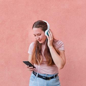 スマートフォンとヘッドフォンを使用して音楽を聴く女性の正面図