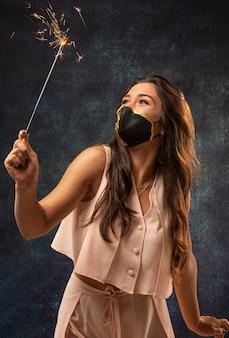 Вид спереди женщины в маске с фейерверком
