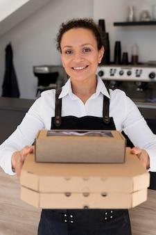 パックされた持ち帰り用食品を保持しているエプロンを着ている女性の正面図