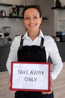テイクアウトのみのサインを保持しているエプロンを着ている女性の正面図 Premium写真