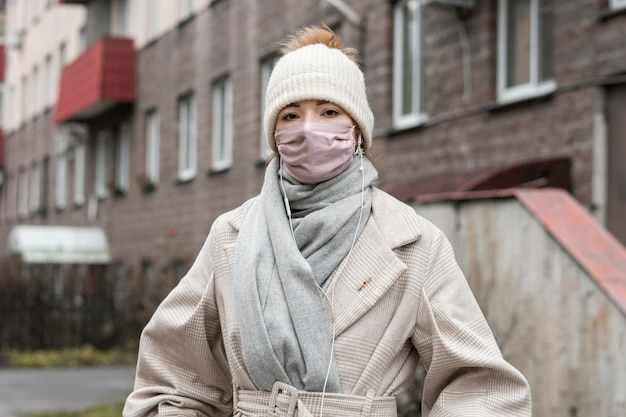 도시에서 의료 마스크를 착용하는 여자의 전면보기