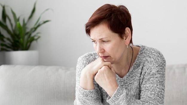 Вид спереди женщины с тревогой на диване