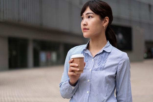 Вид спереди женщины с чашкой кофе