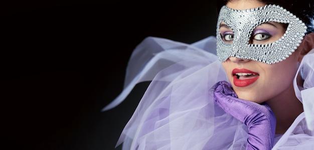 エレガントなカーニバルマスクを持つ女性の正面図