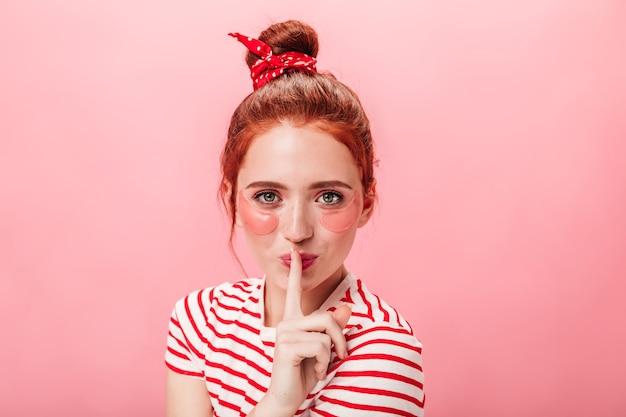 비밀 기호를 보여주는 눈 패치를 가진 여자의 전면 모습. 분홍색 배경에 고립 된 손가락으로 입술을 만지고 생강 소녀의 스튜디오 샷.