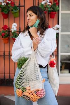 Вид спереди женщины с маской для лица и продуктовыми сумками на открытом воздухе