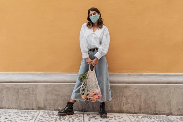 外のフェイスマスクと食料品の袋を持つ女性の正面図