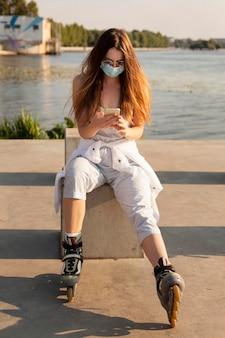 湖のそばのフェイスマスクとローラーブレードを持つ女性の正面図