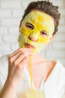 ドリンクを楽しんでいるフェイスマスクを持つ女性の正面図